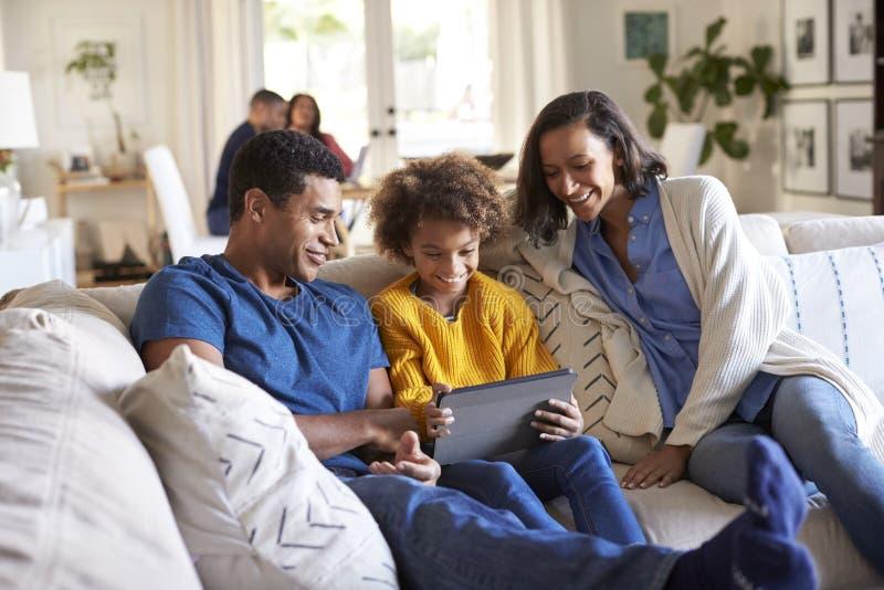 Jonge ouders en hun zitting van de pre-tienerdochter op een bank in de woonkamer die tabletcomputer met behulp van samen, grootou royalty-vrije stock foto's