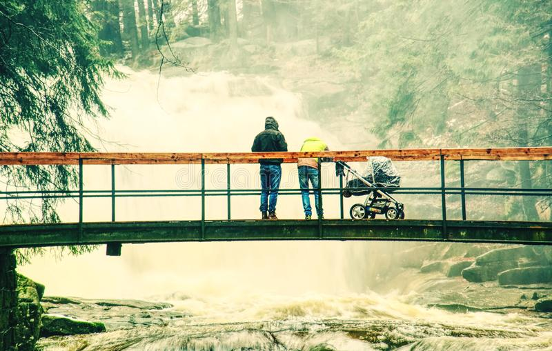 Jonge ouders met baby in kinderwagen op brug over vloedrivier stock afbeeldingen