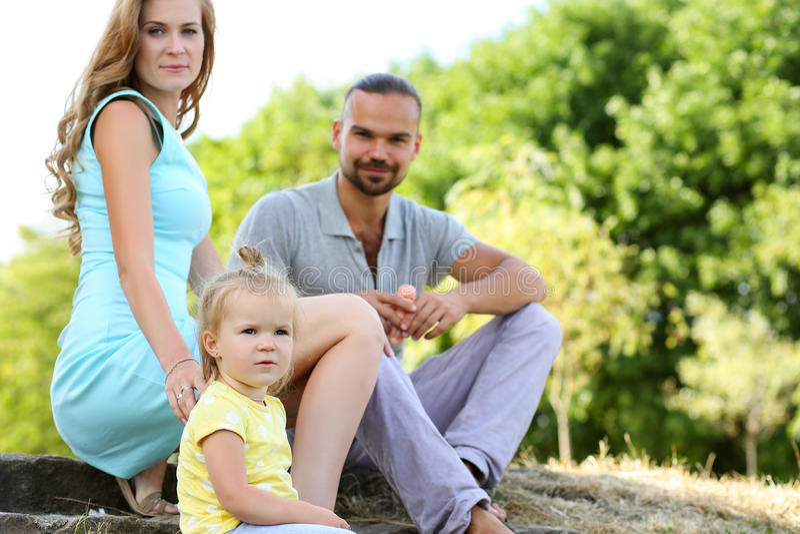 Jonge ouders met dochter op picknick openlucht bij mooie zonnig stock foto