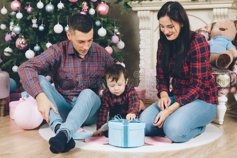 Jonge oudershuiselijke man en vrouw met kind openingskerstmis stock afbeeldingen
