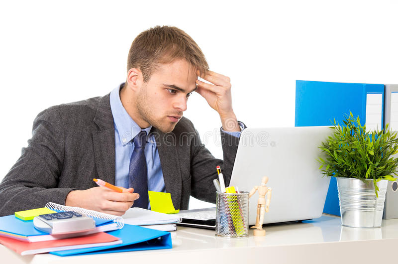 Jonge overgewerkte zakenman het bekijken ongerust gemaakte zitting het bureau van de bureaucomputer in spanning royalty-vrije stock foto's