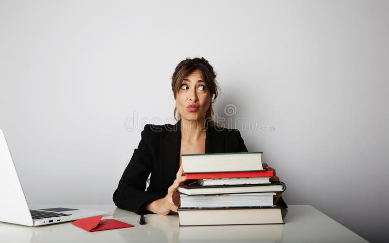 Jonge overweldigde vrouw die hard werken Jonge studenteschok van vele boeken Vrouwelijke modelvoorzijde van reusachtige stapel va royalty-vrije stock foto