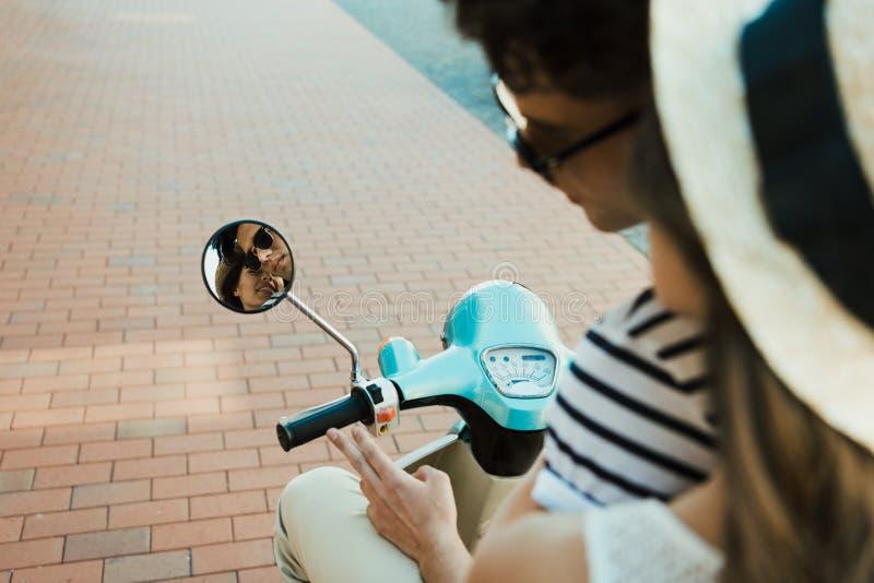 Jonge paar berijdende autoped en het bekijken bezinning in spiegel royalty-vrije stock afbeeldingen
