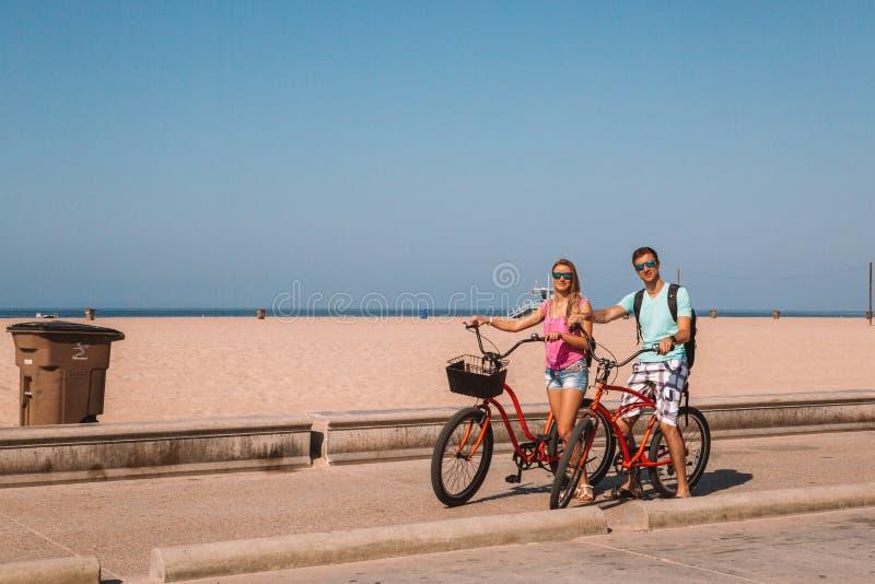 Jonge paar berijdende fietsen onderaan het strand van Venetië in Los Angeles stock foto