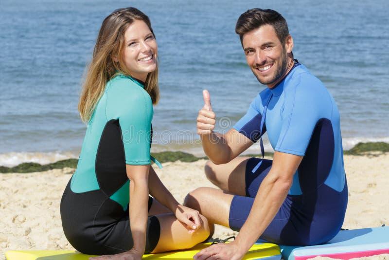 Jonge paar bodyboard surfers die duim-omhoog tonen royalty-vrije stock afbeeldingen