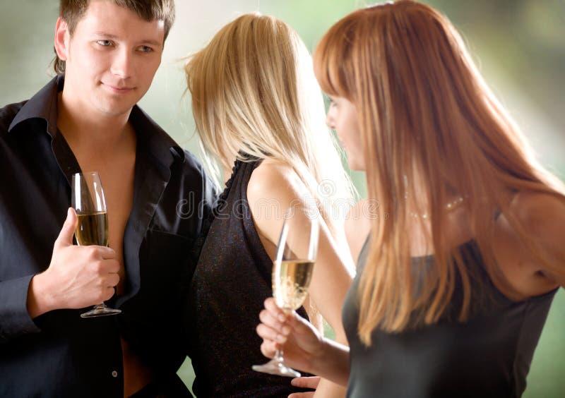 Jonge paar en vrouwen die glazen met champagne houden, in openlucht stock fotografie