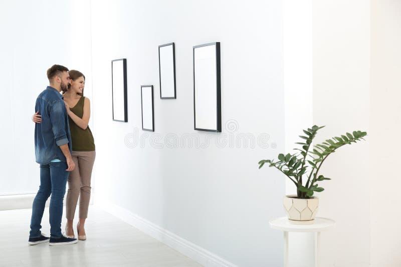 Jonge paar het bekijken expositie in kunstgalerie stock foto's
