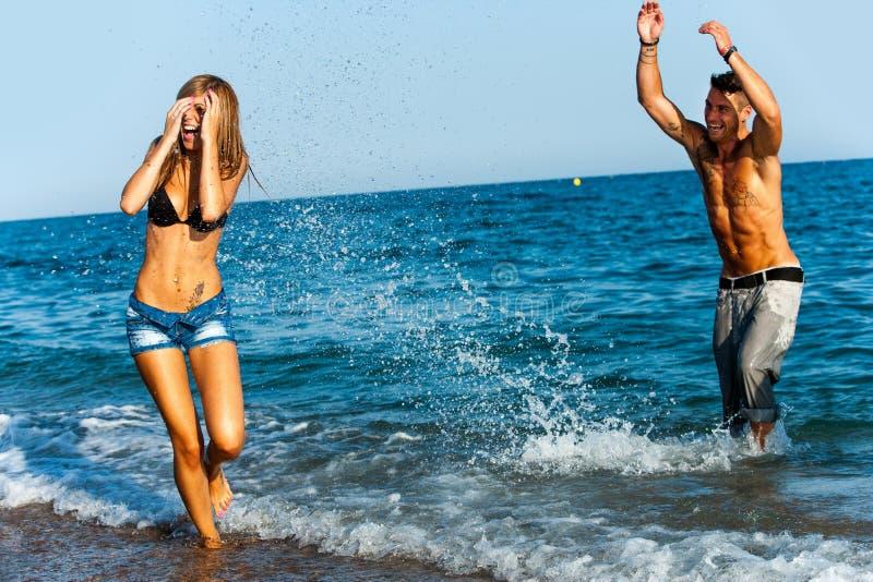 Jonge paar het bespatten water op zee kant. royalty-vrije stock foto's