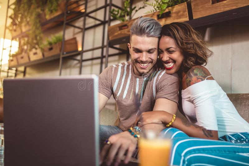 Jonge paar het besteden tijd tussen verschillende rassen in koffie het letten op media royalty-vrije stock foto's