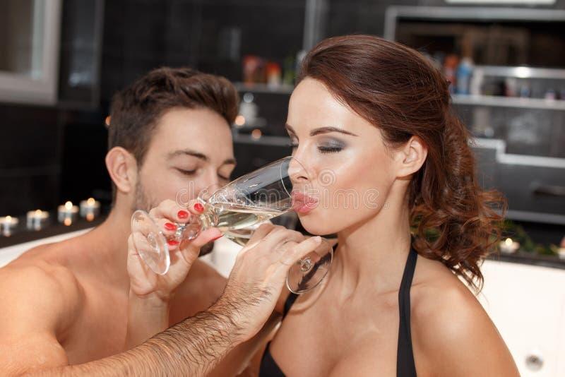 Jonge paar het drinken champagne in Jacuzzi stock foto's
