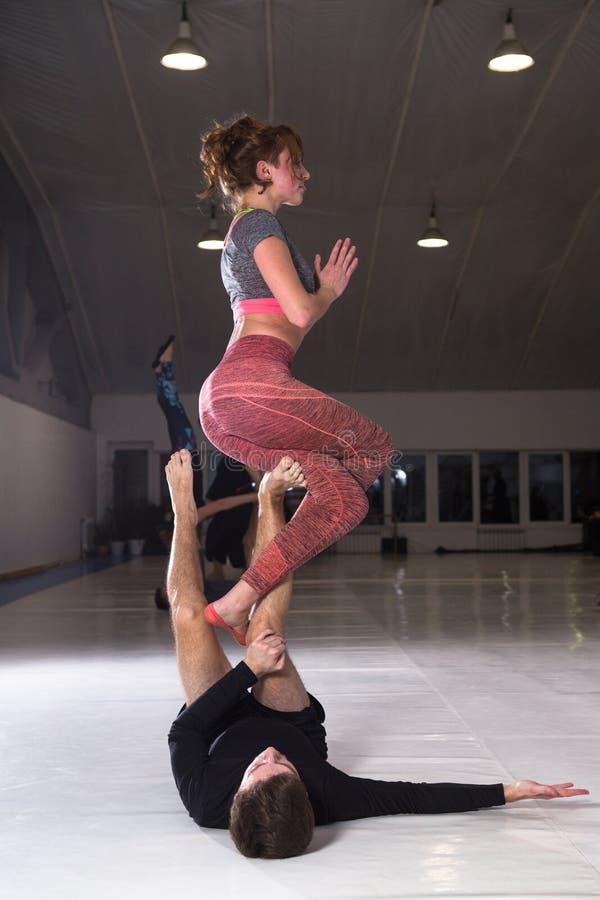 Jonge paar het praktizeren akroyoga op een mat in de gymnastiek samen Vrouwenvliegen Man en vrouwensport de yoga van de opleiding royalty-vrije stock afbeelding
