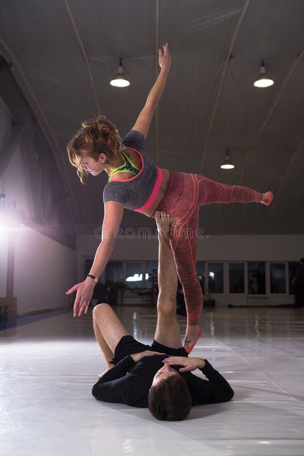 Jonge paar het praktizeren akroyoga op een mat in de gymnastiek samen Vrouwenvliegen Man en vrouwensport de yoga van de opleiding stock fotografie