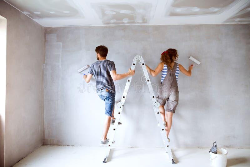Jonge paar het schilderen muren in hun nieuw huis royalty-vrije stock afbeelding