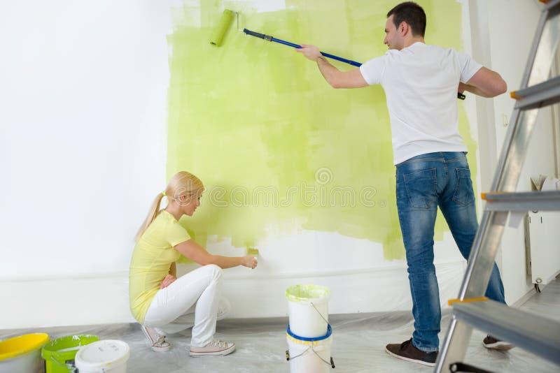 Jonge paar het schilderen muur stock foto's