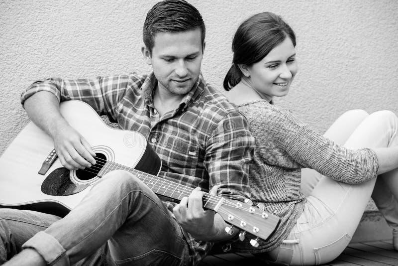 Jonge paar het spelen gitaar stock foto's