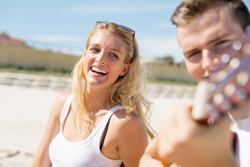 Jonge paar het spelen gitaar op strand in liefde stock foto's