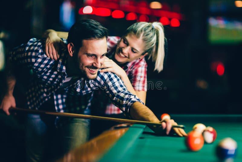 Jonge paar het spelen snooker samen in bar stock afbeeldingen