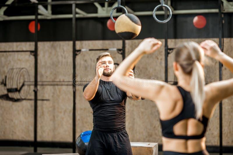 Jonge paar opleiding met bal in de crossfitgymnastiek royalty-vrije stock foto's