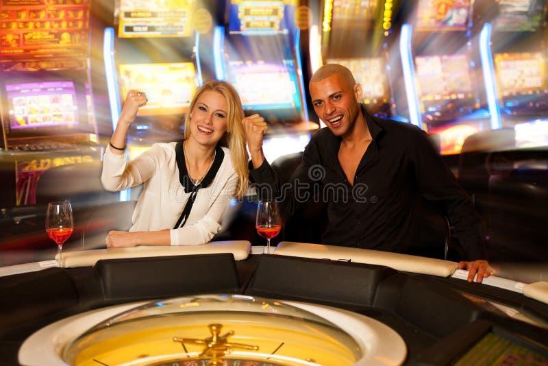 Jonge paar speelroulette in en casino die wedden winnen royalty-vrije stock fotografie