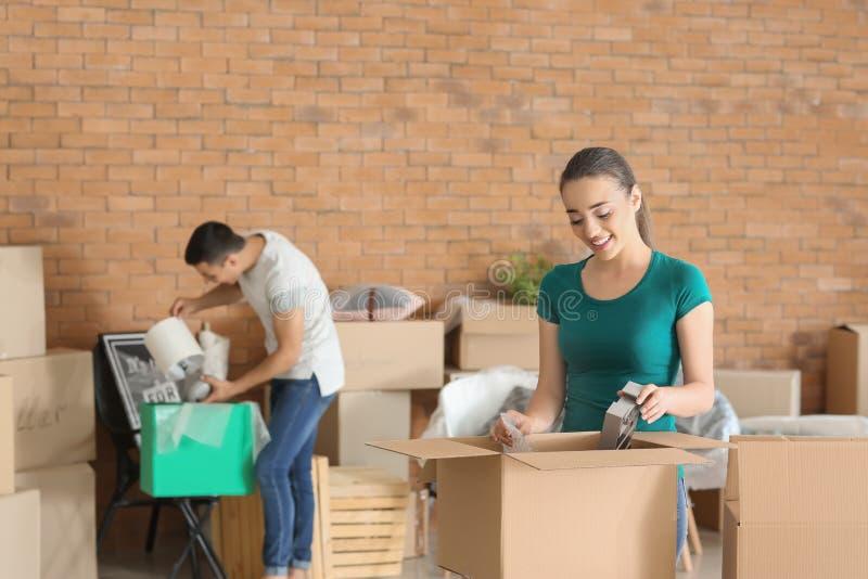 Jonge paar uitpakkende dozen binnen Het bewegen zich in Nieuw Huis stock foto's