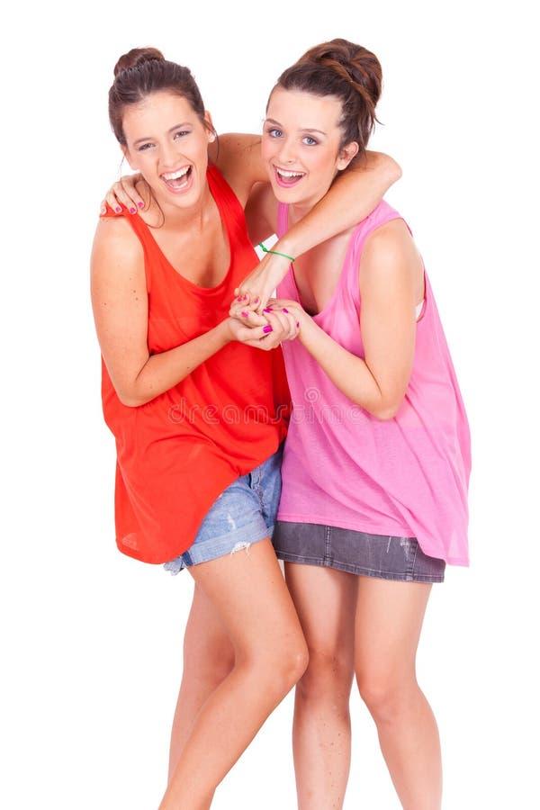 Jonge paar vrouwelijke vrienden die op wit lachen royalty-vrije stock foto