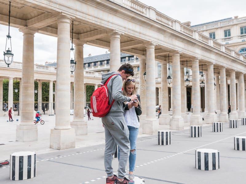 Jonge paarglimlachen bij slimme telefoon bij Palais Royal, Parijs stock foto's