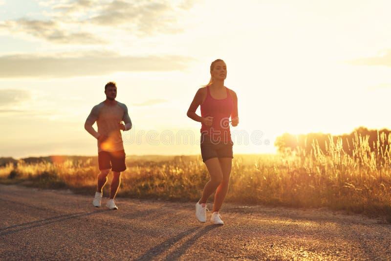 Jonge paarjogging in suberbs na zonsondergang stock foto's