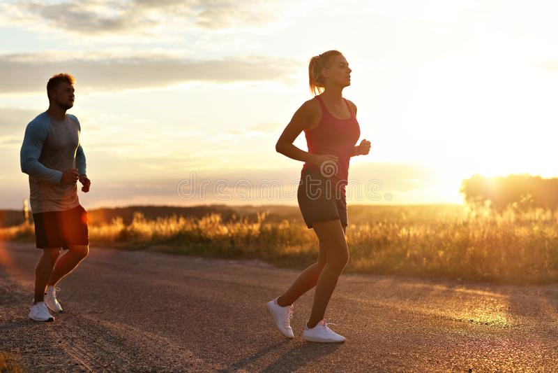 Jonge paarjogging in suberbs na zonsondergang royalty-vrije stock foto's
