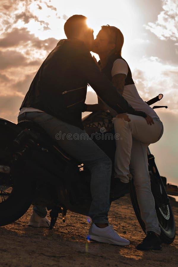 Jonge paarkussen naast een motorfiets royalty-vrije stock foto's