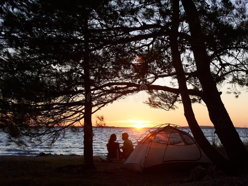 Jonge paarman en vrouw die rust hebben bij toeristentent en kampvuur op overzeese kust branden dichtbij bos stock foto