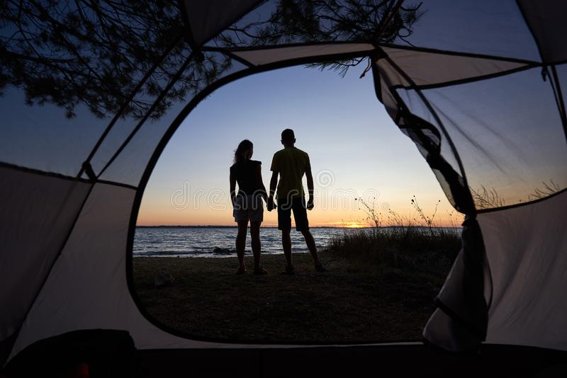 Jonge paarman en vrouw die rust hebben bij toeristentent en kampvuur op overzeese kust branden dichtbij bos royalty-vrije stock fotografie