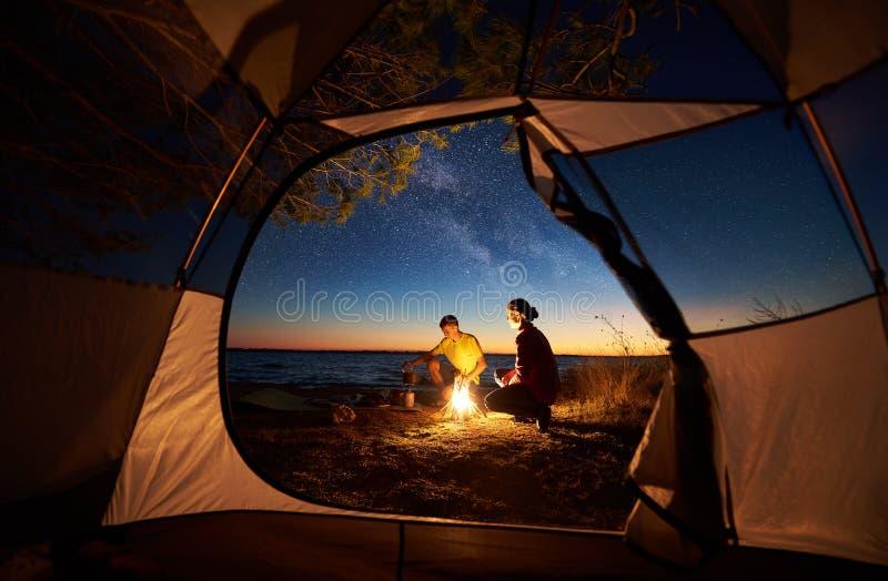 Jonge paarman en vrouw die rust hebben bij toeristentent en kampvuur op overzeese kust branden dichtbij bos stock afbeeldingen