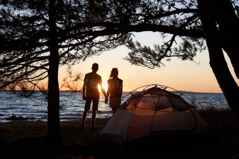 Jonge paarman en vrouw die rust hebben bij toeristentent en kampvuur op overzeese kust branden dichtbij bos stock foto's