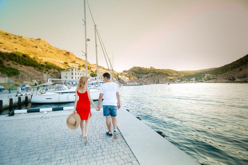 Jonge paaromhelzingen en het ontspannen bij dok dichtbij boot, op zonnige de zomerdag De vrouw en de man in modieuze kleren bevin stock afbeelding