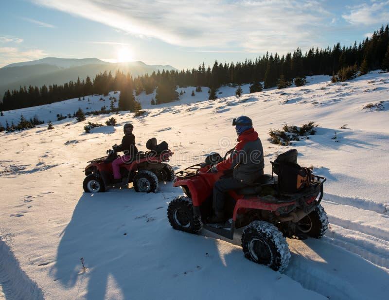 Jonge paarruiters op voertuigen met vier wielenatv fietsen op sneeuw, die van zonsondergang in de bergen in de winter genieten stock afbeeldingen