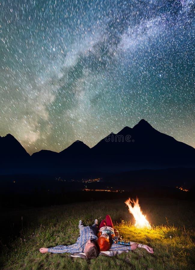 Jonge paartoeristen die dichtbij het kampvuur onder ongelooflijk mooie sterrige hemel en Melkachtige manier bij nacht liggen Laag royalty-vrije stock fotografie