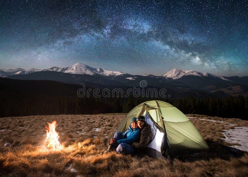 Jonge paartoeristen die een rust in het kamperen hebben bij nacht onder mooie sterrige hemel en melkachtige manier stock fotografie