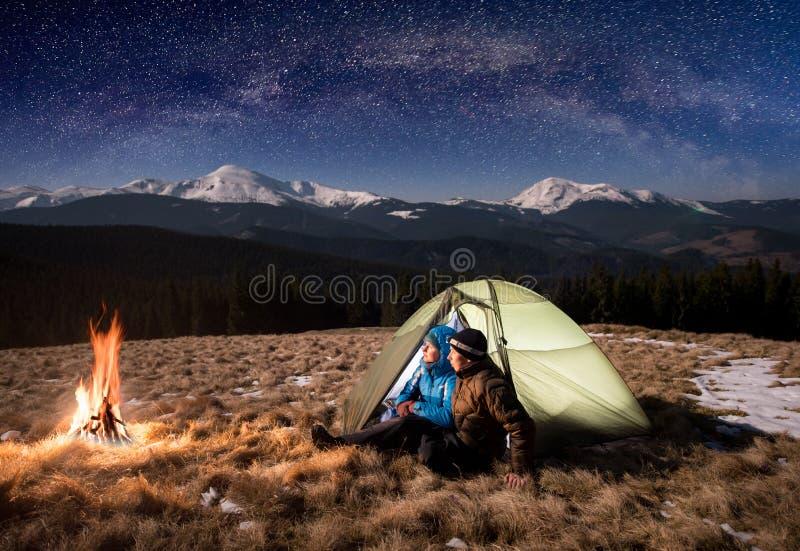 Jonge paartoeristen die in het kamperen bij nacht onder het mooie hoogtepunt van de nachthemel van sterren en melkachtige manier  stock afbeeldingen