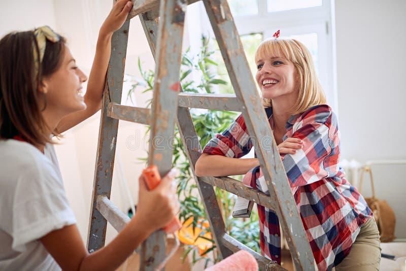 Jonge paarvrouwen die zich in nieuw huis bewegen royalty-vrije stock foto