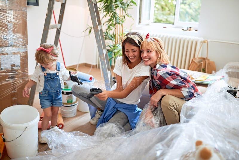 Jonge paarvrouwen die zich in nieuw huis met een peutermeisje bewegen stock afbeelding