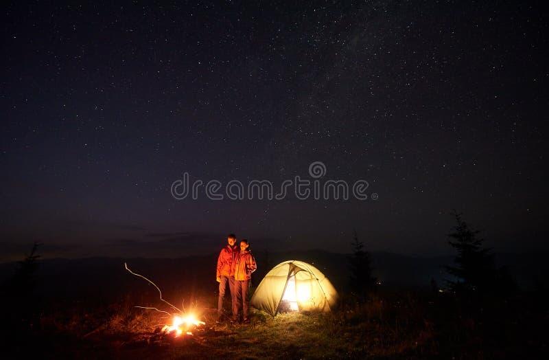 Jonge paarwandelaars die dichtbij verlichte tent rusten, die in bergen bij nacht onder sterrige hemel kamperen stock afbeeldingen