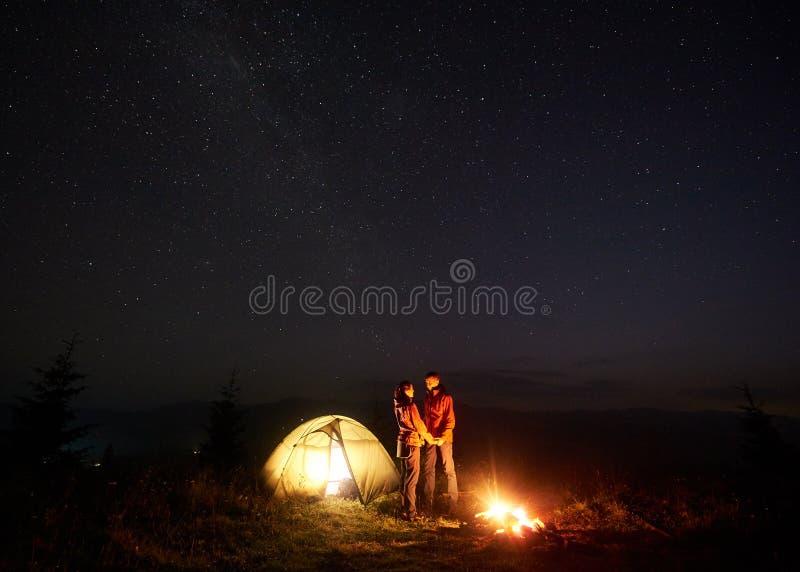 Jonge paarwandelaars die dichtbij verlichte tent rusten, die in bergen bij nacht onder sterrige hemel kamperen stock foto