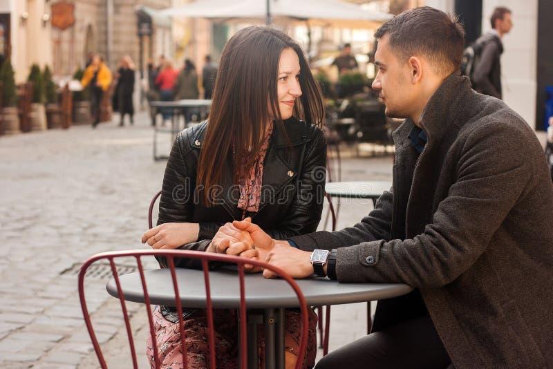 Jonge paarzitting bij de straatkoffie Romantische datum stock fotografie