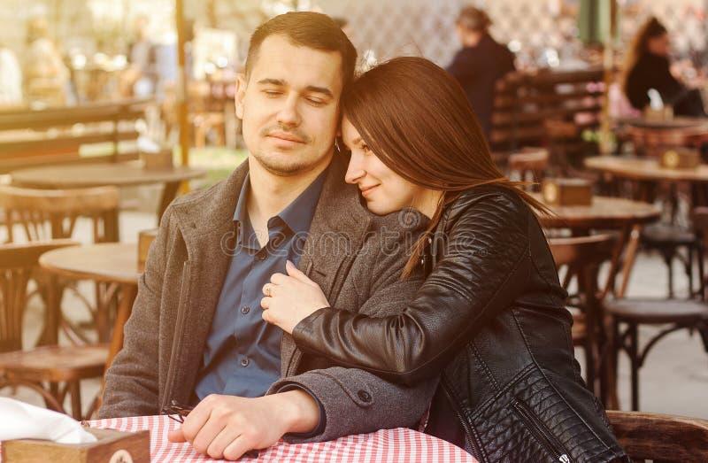 Jonge paarzitting bij de straatkoffie in de zongloed Romantische datum royalty-vrije stock afbeelding