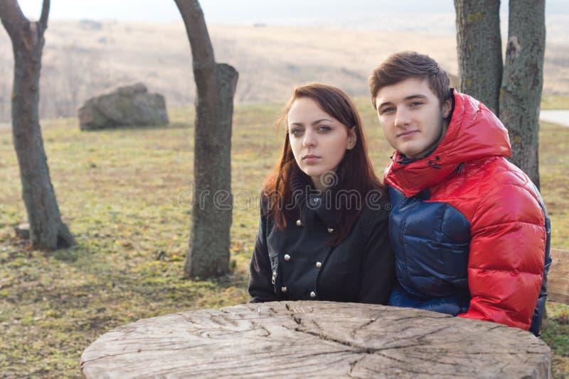 Jonge paarzitting bij een rustieke picknicklijst royalty-vrije stock foto