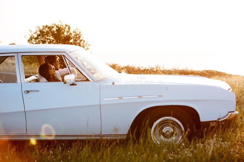 Jonge paarzitting binnen retro auto stock foto's