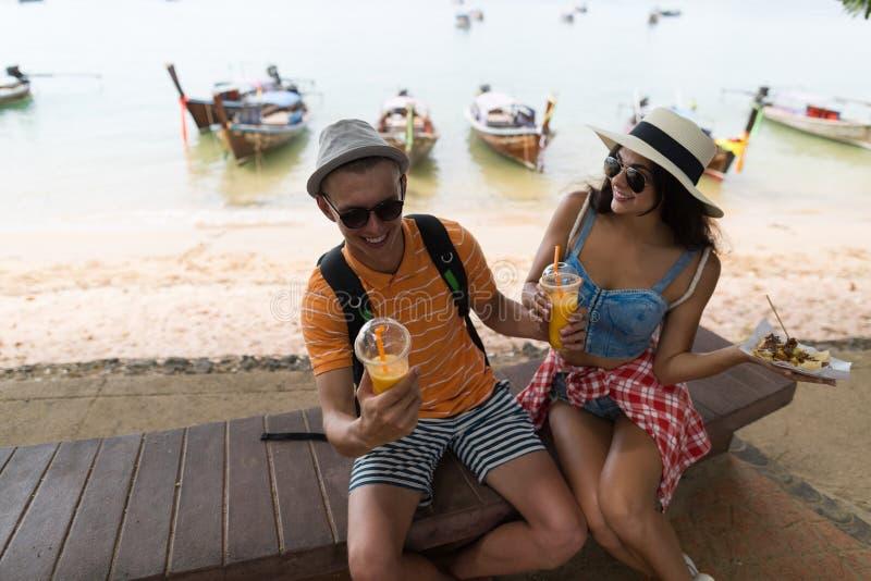 Jonge Paarzitting dichtbij Strand Straatvoedsel eten en Vers Sap drinken, de Gelukkige Glimlachende Mens en Vrouwentoeristen die royalty-vrije stock fotografie