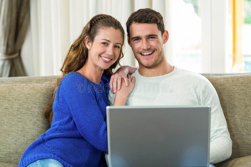 Jonge paarzitting op bank en het gebruiken van laptop stock afbeeldingen