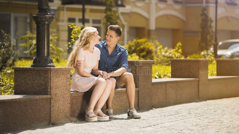 Jonge paarzitting op bank en holdingshanden, kerel in liefde die meisje koesteren royalty-vrije stock fotografie