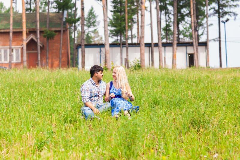 Jonge paarzitting op gras en het ontspannen stock foto's